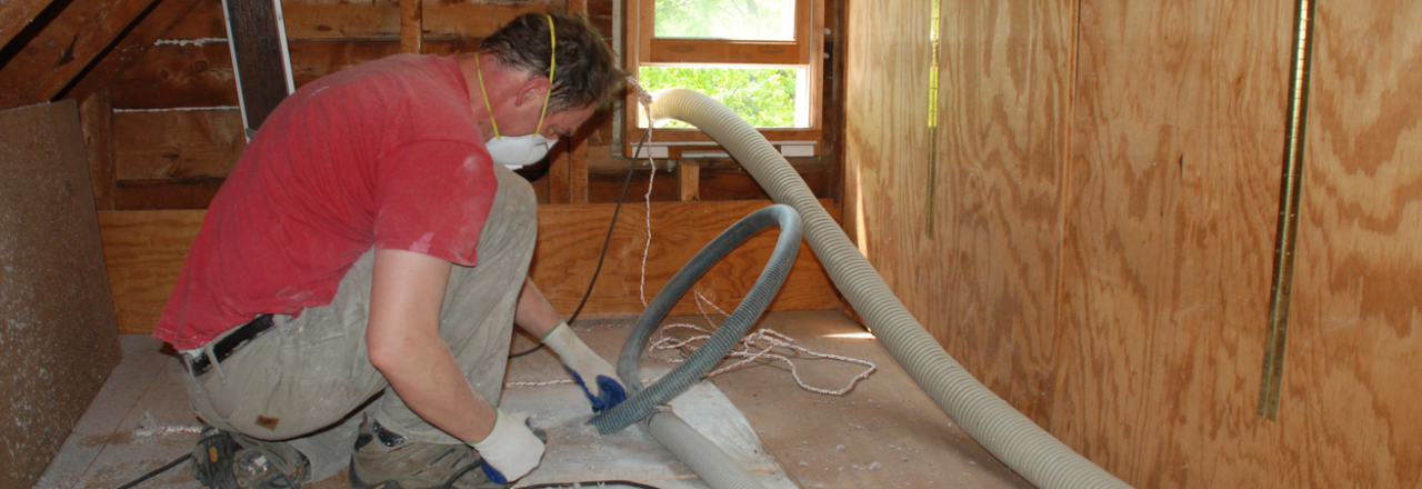 Employee from The Breathable Home putting vacuums in place to remove insulation